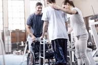 Physical therapists helping man with walker - CAIF11355