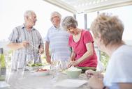 Senior couples preparing patio lunch - CAIF11367