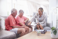 Financial advisor discussing paperwork with senior couple - CAIF11406