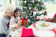 Smiling mother and daughter with Christmas gift - CAIF11424