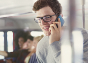 Smiling man with eyeglasses talking on cell phone on bus - CAIF11433