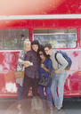 Friends taking selfie next to double-decker bus - CAIF11454