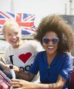 Portrait enthusiastic friends with British flag riding double-decker bus - CAIF11466