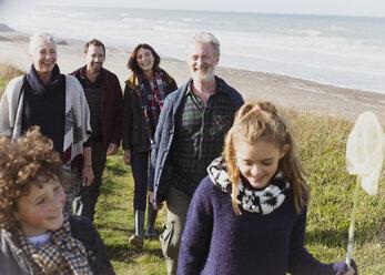 Multi-generation family walking on grassy beach path - CAIF11487