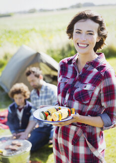 Portrait smiling woman with vegetable skewers at campsite - CAIF11490