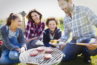 Family barbecuing at sunny campsite - CAIF11502