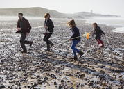 Family running on rocky beach - CAIF11505