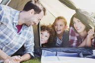 Smiling family in tent - CAIF11508