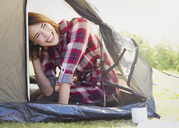 Smiling woman inside tent - CAIF11514