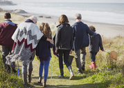 Multi-generation family walking on sunny grass beach path - CAIF11535