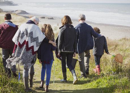 Multi-generation family walking on sunny grass beach path - CAIF11535