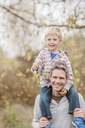 Portrait smiling father carrying toddler son on shoulders in autumn park - CAIF11541