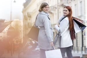 Portrait of smiling women with shopping bags on city sidewalk - CAIF11556