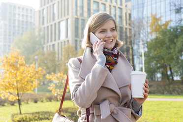 Smiling businesswoman with coffee talking on cell phone in city park - CAIF11562