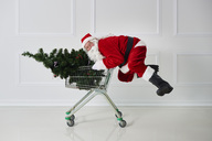 Happy Santa Claus carrying Christmas tree in a shopping cart - ABIF00107