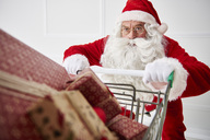 Portrait of Santa claus with shopping cart of Christmas presents - ABIF00110