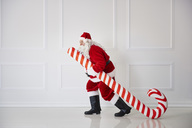Santa Claus carrying oversized candy cane - ABIF00113