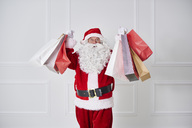 Portrait of Santa claus holding shopping bags - ABIF00122
