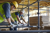 Construction workers adjusting metal bar at construction site - CAIF11591
