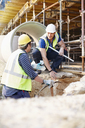 Construction workers talking at construction site - CAIF11597