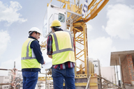 Construction worker and engineer reviewing blueprints below crane at construction site - CAIF11606