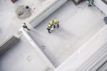 Overhead view of construction workers and engineers at construction site - CAIF11609