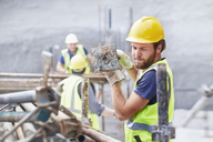Construction worker carrying metal bar at construction site - CAIF11618