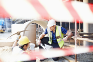 Construction workers talking at construction site - CAIF11624