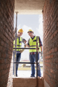 Construction workers texting with cell phone at construction site - CAIF11630