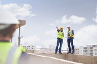 Construction worker and engineer talking at highrise construction site - CAIF11636