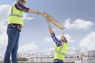 Construction workers lifting part at highrise construction site - CAIF11645