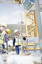Construction workers assembling structure at highrise construction site - CAIF11648