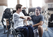 Physical therapist fist bumping man in wheelchair - CAIF11684