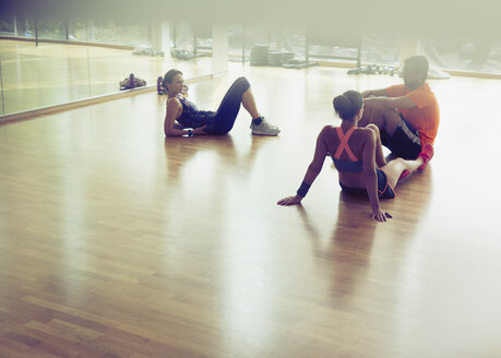 Friends resting and talking on gym studio floor - CAIF11693