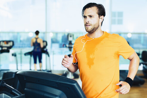Sweating man with headphones running on treadmill at gym - CAIF11699