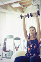 Focused woman doing dumbbell shoulder presses at gym - CAIF11708