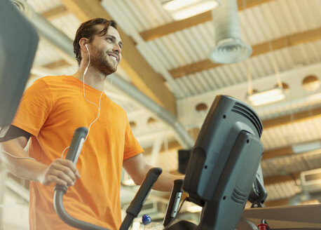 Smiling man with headphones using elliptical trainer at gym - CAIF11711