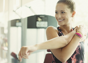 Smiling woman stretching arm at gym - CAIF11720
