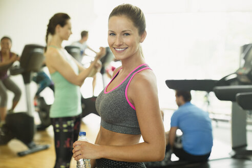 Portrait smiling woman resting at gym - CAIF11723