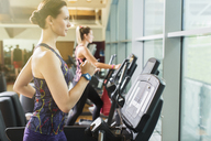 Focused woman running on treadmill at gym - CAIF11726