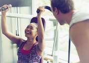 Personal trainer encouraging woman using exercise equipment at gym - CAIF11732