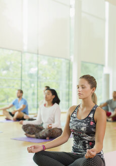Serene woman in lotus position with eyes closed in yoga class - CAIF11741