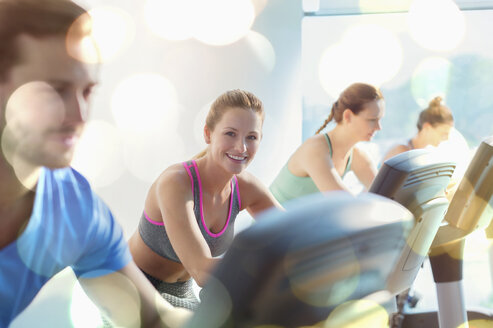 Smiling woman riding exercise bike at gym - CAIF11753