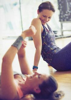 Smiling women resting on gym studio floor - CAIF11762