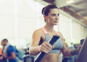 Focused woman exercising on elliptical trainer in gym - CAIF11765
