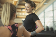 Smiling women talking at gym - CAIF11771