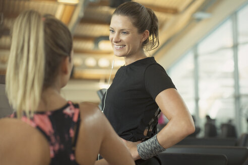 Smiling women talking at gym - CAIF11771