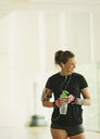 Smiling woman taking a break drinking water in gym studio - CAIF11774