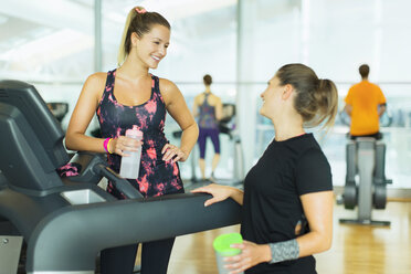 Smiling women resting and talking at treadmill in gym - CAIF11777