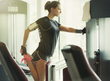 Focused woman stretching leg at exercise equipment in gym - CAIF11783